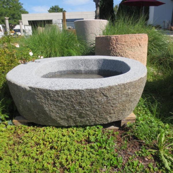 Granitbrunnen aus graunem Granit. Der Brunnen stammt aus Bayern, es handelt sich um einen bayrischen Granit